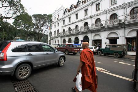 Un monaco buddista vicino al Queen's Hotel immerso nel traffico. Antico e moderno a Sry lanka si mescolano continuamente.